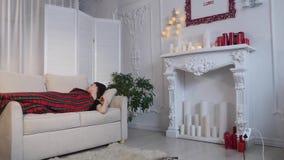 Mujer joven que duerme en el sofá en casa almacen de metraje de vídeo