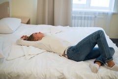 Mujer joven que duerme en el sofá en sala de estar Foto de archivo libre de regalías