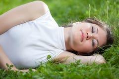 Mujer joven que duerme en hierba Imagen de archivo libre de regalías