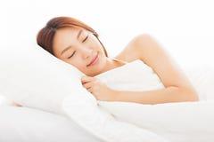 Mujer joven que duerme en la cama Fotos de archivo