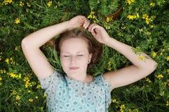Mujer joven que duerme en un prado de la flor Foto de archivo