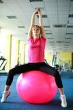 Mujer joven que ejercita con la bola de la aptitud Imagen de archivo