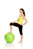 Mujer joven que ejercita con la bola de los pilates Fotografía de archivo
