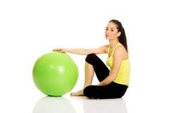 Mujer joven que ejercita con la bola de los pilates Imagen de archivo