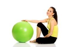 Mujer joven que ejercita con la bola de los pilates Imagenes de archivo