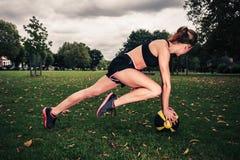 Mujer joven que ejercita con la bola de medicina en parque Fotos de archivo libres de regalías