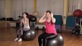 Mujer joven que ejercita con la bola suiza Clase de la bola de la aptitud almacen de video