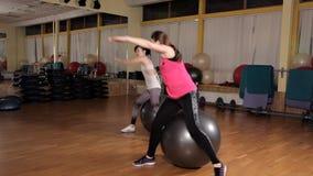 Mujer joven que ejercita con la bola suiza Clase de la bola de la aptitud metrajes