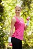 Mujer joven que ejercita con pesas de gimnasia Foto de archivo libre de regalías