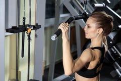 Mujer joven que ejercita detrás en la máquina en el gimnasio y que dobla los músculos - modelo atlético muscular de la aptitud de fotografía de archivo libre de regalías