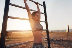 Mujer joven que ejercita en barras de pared al aire libre fotografía de archivo libre de regalías