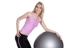 Mujer joven que ejercita en bola de la aptitud Fotos de archivo libres de regalías