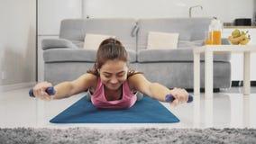 Mujer joven que ejercita en casa en una sala de estar metrajes