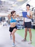 Mujer joven que ejercita en gimnasio Imagen de archivo