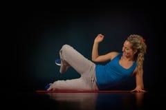 Mujer joven que ejercita en la gimnasia Imagenes de archivo