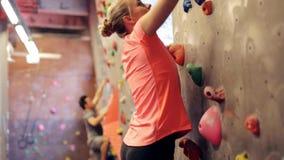 Mujer joven que ejercita en la pared interior del gimnasio que sube metrajes