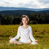 Mujer joven que ejercita la yoga al aire libre Fotografía de archivo libre de regalías