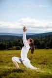 Mujer joven que ejercita la yoga al aire libre Fotos de archivo