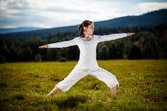 Mujer joven que ejercita la yoga al aire libre Imágenes de archivo libres de regalías