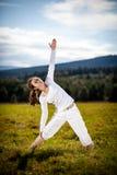 Mujer joven que ejercita la yoga al aire libre Fotografía de archivo