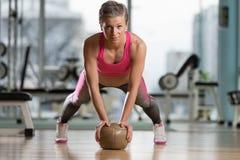 Mujer joven que ejercita pectorales en bola de medicina Imagen de archivo libre de regalías