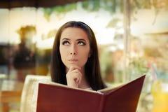 Mujer joven que elige de un menú del restaurante imagenes de archivo