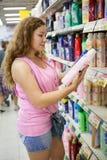 Mujer joven que elige el detergente de la limpieza en tienda Imagen de archivo