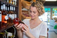 Mujer joven que elige el vino rosado en licorería imágenes de archivo libres de regalías
