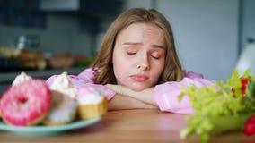 Mujer joven que elige entre las verduras y los dulces Mirada triste de la muchacha metrajes