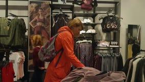 Mujer joven que elige la ropa en la alameda almacen de metraje de vídeo