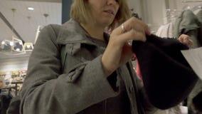 Mujer joven que elige la ropa en la alameda almacen de video