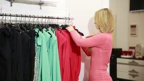 Mujer joven que elige la ropa en un estante en una sala de exposición metrajes