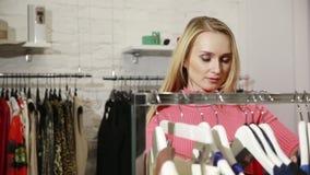 Mujer joven que elige la ropa en un estante en una sala de exposición almacen de video