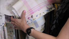 Mujer joven que elige la tela interesante en tienda de la materia textil metrajes