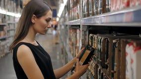 Mujer joven que elige una botella de zumo de frutas en el supermercado, madre joven de la mamá en tienda metrajes