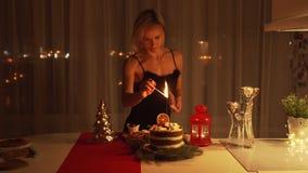 Mujer joven que enciende una bengala en la torta en la noche en el tiempo de la Navidad metrajes