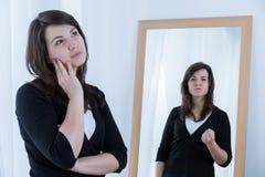 Mujer joven que enmascara sus emociones Foto de archivo