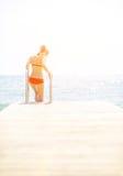 Mujer joven que entra abajo el mar del puente Fotografía de archivo