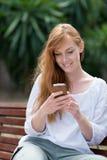 Mujer joven que envía SMS Imagen de archivo