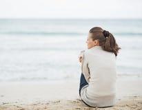 Mujer joven que envuelve en suéter mientras que se sienta en la playa sola Fotos de archivo libres de regalías