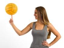 Mujer joven que equilibra una bola en su finger Imagenes de archivo