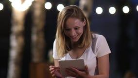 Mujer joven que es sorprendida y feliz al usar una tableta digital almacen de video