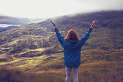 Mujer joven que es una con la naturaleza en el top de la montaña Foto de archivo