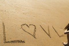 Mujer joven que escribe el amor de la palabra en la arena de una playa hermosa Imagen de archivo