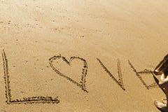 Mujer joven que escribe el amor de la palabra en la arena de una playa hermosa Fotos de archivo