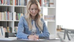 Mujer joven que escribe la letra en el trabajo, papeleo almacen de metraje de vídeo