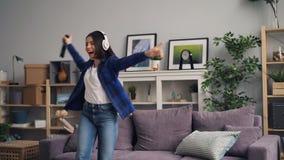 Mujer joven que escucha el baile del canto de la música en el hogar que salta en el sofá metrajes
