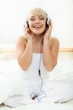 Mujer joven que escucha la música Imagenes de archivo