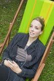 Mujer joven que escucha la música Fotos de archivo