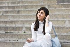 Mujer joven que escucha la música Imágenes de archivo libres de regalías